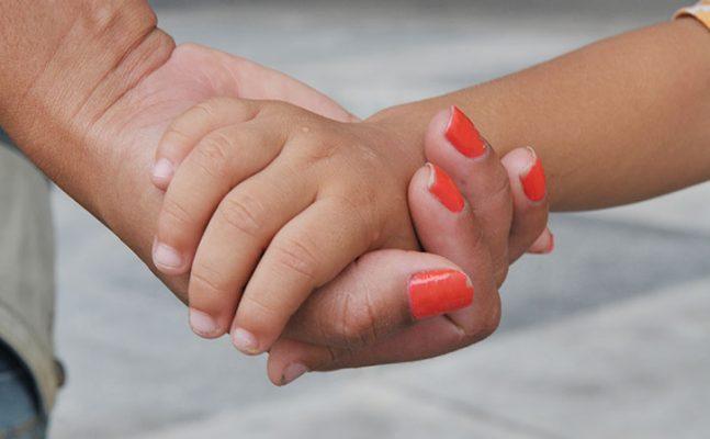 a mão de um adulto segurando a mão de uma criança